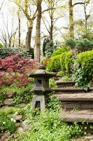 Small tōrō lantern on stone platform next to steps in garden