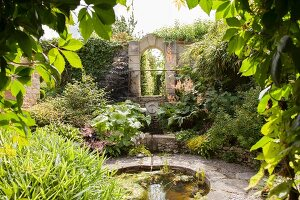 Round pool surrounded by stone terrace in flowering garden