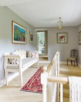 Traditional white bench next to bannister on landing with walls painted pale grey
