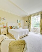 Double bed with upholstered headboard in bedroom painted pale yellow