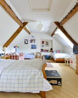 Three beds in converted attic bedroom with exposed wooden beams