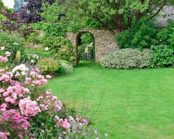Clipped lawn, flowering shrubs and wrought iron gate in garden wall