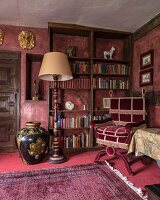 Standard lamp, velvet reading chair and bookcase in grand library