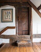 Antique wooden steps leading to rustic, restored wooden door in attic