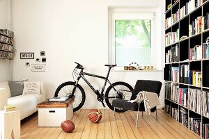 Bookcase, bicycles and old vaulting box used as coffee table in living room