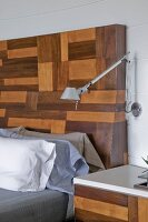 Tolomeo wall-mounted lamp above bedside table and bed with elaborate, modern wooden headboard