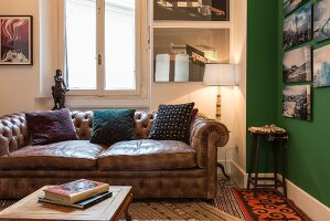 Scatter cushions on vintage leather sofa next to landscape photos on green wall