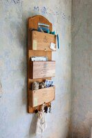 Old cigar boxes mounted on wooden board and repurposed and organiser with key rack