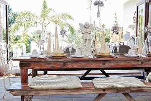 Dining table festively set with angel figurines in vintage-style interior