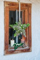 A Christmas window star made of conifer sprigs and clematis fruits hung by a rustic wooden in candle light