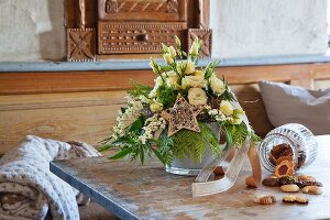A Christmas table decoration with Japanese roses on a rustic table