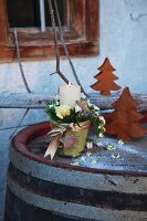 A candle decoration with flowers and a ribbon in a pot on a vintage barrel with decorative wooden trees