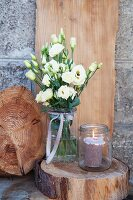 A festive bouquet of Japanese flowers in a jar decorated with a ribbon on a slice of bark with a lantern