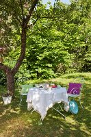 Ornate metal chairs around table set with crocheted tablecloth under shady tree