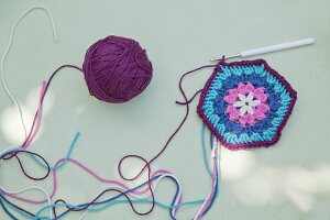 Crocheted floral hexagon in shades of blue and purple