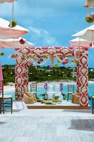Indian outdoor wedding on platform; pergola decorated with flowers above chairs with white loose covers for bride and groom in front of sea coast