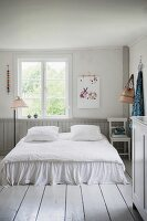 Romantic double bed on white wooden floor in rustic bedroom with vintage-style ambiance