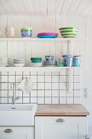 Crockery on bracket shelves above kitchen counter and white-tiled splashback
