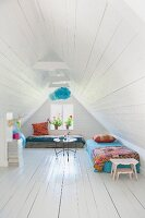 White wood-clad walls, ceiling and floor and colourful throws on couches in converted attic