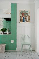 Pastellgrüner Stuhl vor weisser Holzverkleidung neben grün gefliestem Kochbereich in skandinavischer Küche