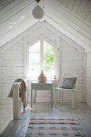 Tisch und Stuhl vor Giebelfenster im Dachgeschoss mit weisser Holzverschalung