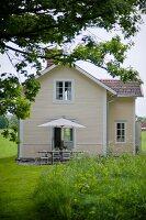 Landhaus mit hellgelb gestrichener Holzfassade und Terrassenplatz mit Sonnenschirm hinter blühender Sommerwiese