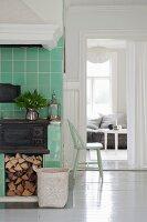 Gusseiserner Küchenofen mit Holzlager in grün gefliestem Kochbereich und offener Durchgang mit Blick ins Wohnzimmer
