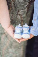 Couple holding tiny baby shoes in interlinked hands