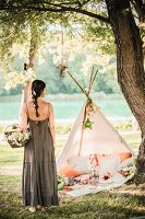 Woman wearing long summer dress holding basket of flowers in front of romantic picnic in teepee