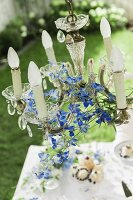 Crystal chandelier decorated with delphiniums hung over coffee table in garden