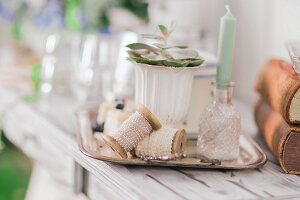 Reels of ribbon, candle in crystal vase and succulent in china goblet