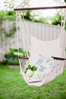 White hydrangea flowers and floral cushion in hanging chair in garden