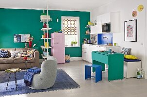 A kitchen and a living area in a brightly coloured apartment