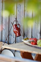 Red jug hanging on metal frame against wooden wall; lunch on table in blurred foreground