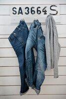 Jeanshosen und ein Pulli an einer Hakenleiste an Bretterwand