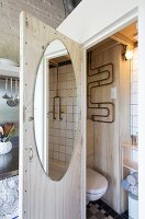 Oval mirror on toilet door