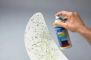 Decorating a chair backrest with splashes of paints and fixing with clear spray lacquer