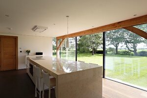 Free-standing polished stone kitchen counter and view of garden through panoramic glass wall