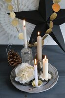 Christmas decorations and Advent wreath; four lit candles in various holders around paper flower in front of garland of gold paper discs