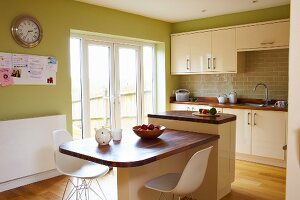 White classic shell chairs at table with wooden top abutting island counter in kitchen with green-painted walls