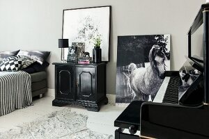 Piano, cabinet and photo of horse leant against wall in monochrome bedroom