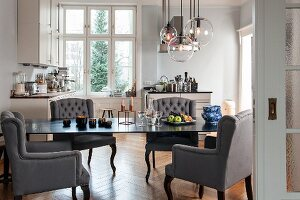 Postmodern armchair with grey covers around table in modern kitchen