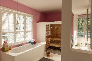 Bathtub below window in spacious bathroom with sauna