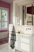 Pattern of light and shade on washstand with white base unit and wall-mounted tap below mirror in niche