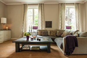 Coffee table and corner couch in front of windows in elegant beige interior