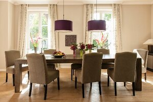 Elegant upholstered chairs around long, solid-wood table below pendant lamps in dining room