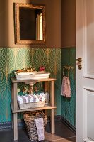 Sink on wooden frame against dado with turquoise and gold patterned wallpaper below gilt-framed mirror on brown-painted wall
