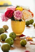 Roses in vintage vase and green apples on wooden table