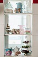 Decorative, vintage-style kitchen utensils on white shelves in window