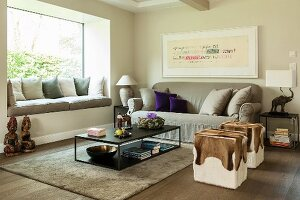 Animal-skin pouffes, grey sofa, modern coffee table and window seat with scatter cushions